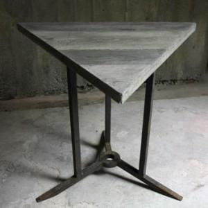 Table en béton triangulaire, piètement métal.